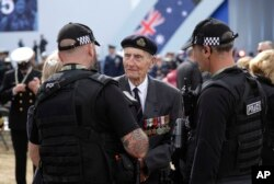British D-Day veteran Jim Booth speaks to police officers as he arrives for an event to mark the 75th anniversary of D-Day in Portsmouth, England, June 5, 2019.