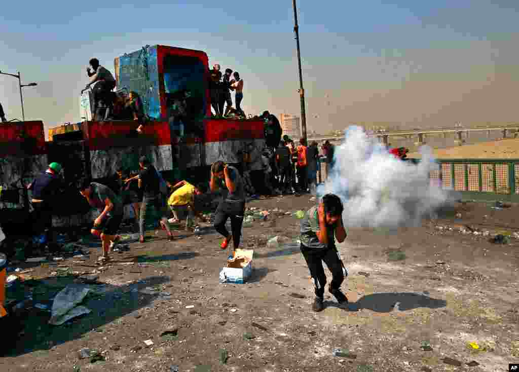 Security forces fire sound bombs to disperse anti-government protesters on the closed Joumhouriya Bridge that leads to the Green Zone government areas, near Tahrir square, Baghdad, Iraq.