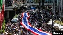 2014年1月13日,泰國反政府抗議者打著巨幅國旗遊行走過曼谷市中心購物區。