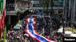 Demonstran anti-pemerintah berbaris membawa bendera Thailand raksasa di daerah perbelanjaan di pusat kota Bangkok (13/1). (Reuters/Nir Elias)