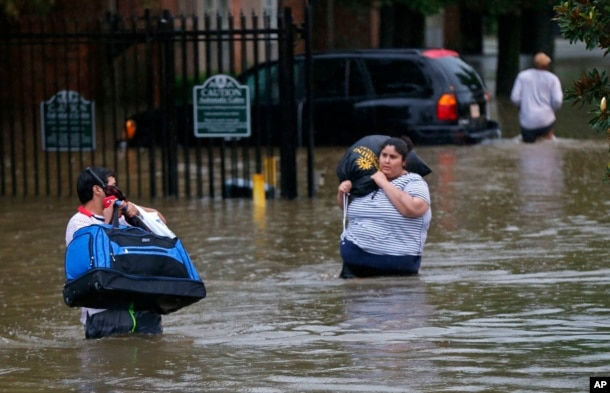 FILE - Residents wade through floodwater in the Chateau Wein Apartments in Baton Rouge, Louisiana, Aug. 12, 2016.