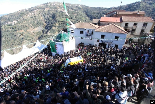 The ambulance convoy carrying the coffin of Hocine Ait Ahmed, a national hero of the independence war with France, arrives for a burial ceremony in Ath Ahmedh, Algeria, amid a crush of thousands seeking to pay respects, Jan.1, 2016.