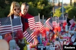 "FILE - A couple looks over 58 wooden crosses, with the names and photos of the October 1 mass shooting victims, in the median of Las Vegas Boulevard South near the ""Welcome to Las Vegas"" sign in Las Vegas, Nevada, Oct. 9, 2017."