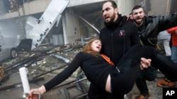 Чоловік несе поренену вибухом жінку.