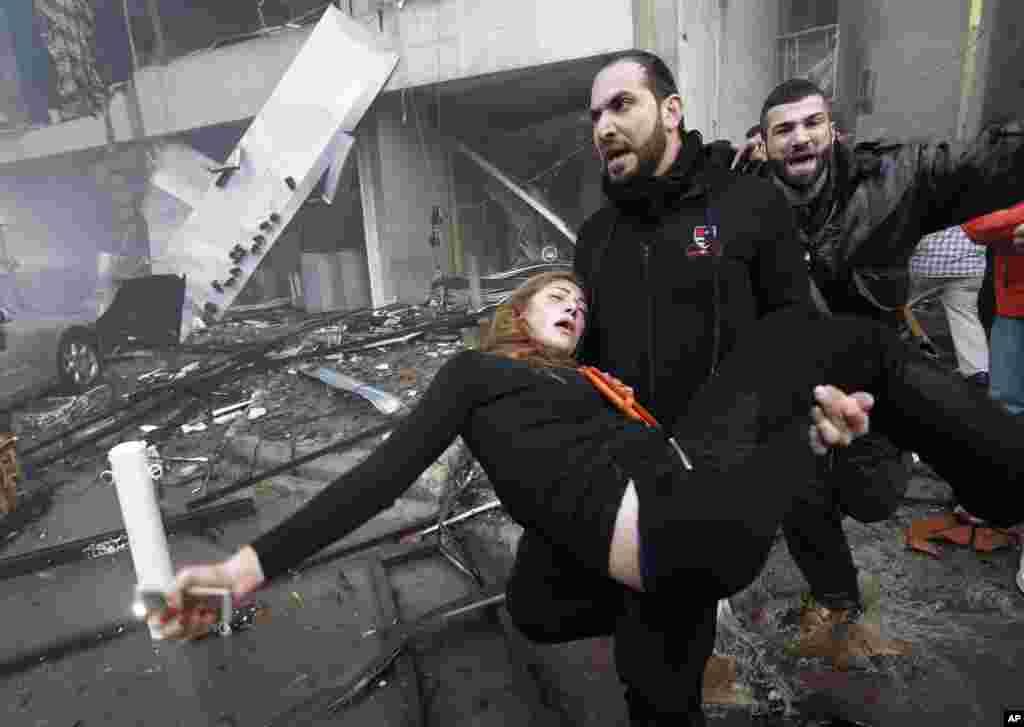 Beyrutda bomba partlayışı zamanı yaralanmış qadına yardım edilir - 2 yanvar, 2014