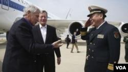 美國國防部長哈格爾(左)抵達青島國際機場,受到美國駐華大使博卡斯和中國國防部外事辦公室主任關友飛少將的歡迎。