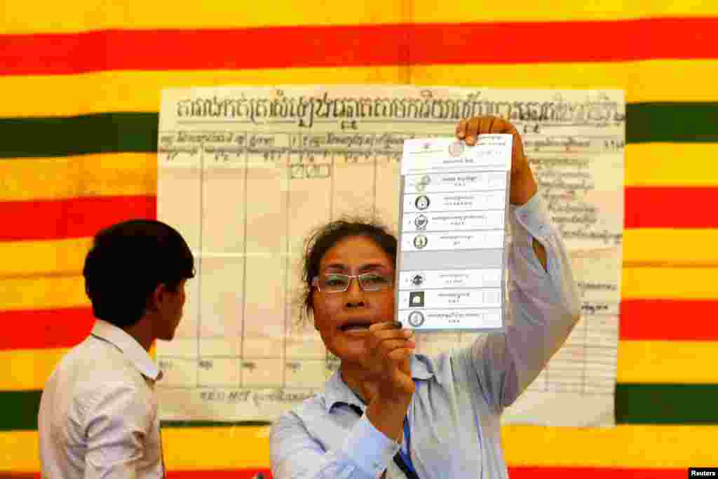An election official shows a ballot paper in Phnom Penh, July 28, 2013.