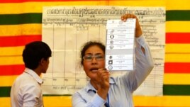 FILE - An election official shows a ballot paper in Phnom Penh, July 28, 2013.
