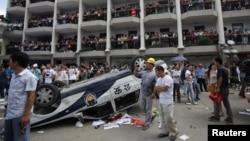 Para pengunjuk rasa membalikkan mobil polisi sebagai bagian dari aksi protes atas rencana pemerintah membangun pipa limbah industri di Qidong, propinsi Jiangsu (28/7).