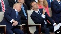 Los presidentes Donald Trump y Emmanuel Macron observan el vuelo de los aviones durante el desfile del Día de Bastilla en Paris.