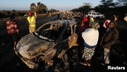 Relatives and civilians look at the wreckage of cars burned when a tanker crashed into several vehicles and killed several people, near the Rift Valley town of Naivasha, west of Kenya's capital, Nairobi, Dec. 11, 2016.