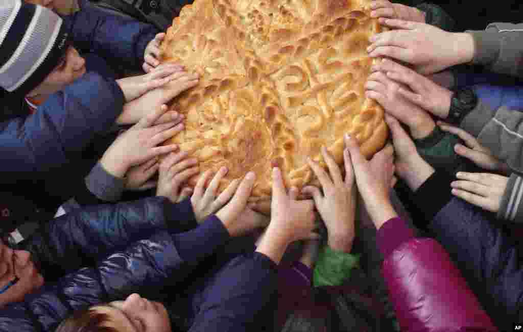Bosnian Serb children break the traditional Christmas bread to mark Orthodox Christmas Day festivities in Banja Luka ,140 kilometers northwest of Sarajevo, Bosnia, Saturday, Jan. 7, 2012. (AP)