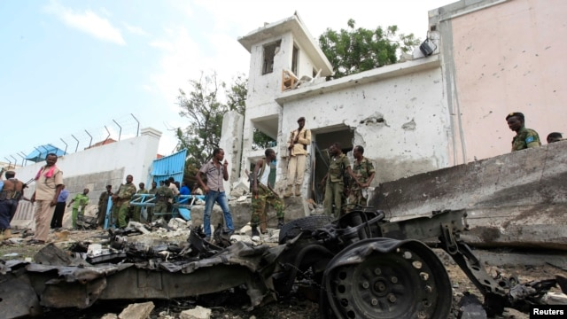 Security agents stand near the scene of a suicide bomb attack outside the United Nations compound in Somalia's capital Mogadishu, June 19, 2013.