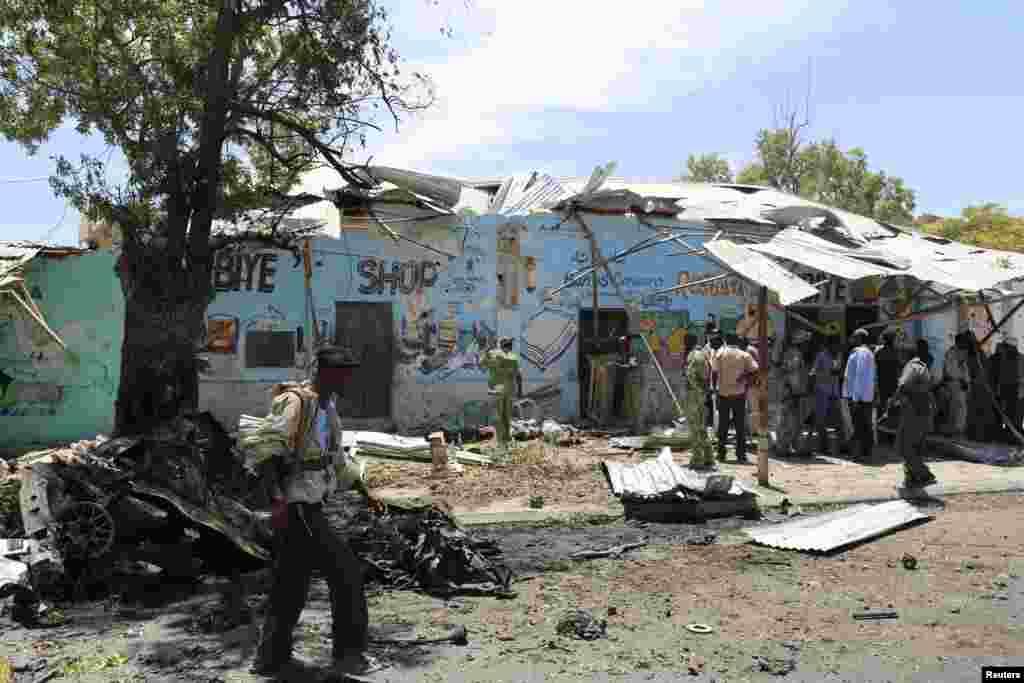Um agente da polícia caminha pelo local onde um carro-bomba explodiu junto a um café em Mogadíscio, Somália, Fev. 27, 2014.