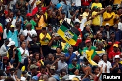 FILE - Supporters of the ANC wave a flag during the party's 106th anniversary celebrations, in East London, South Africa, Jan. 13, 2018. Analysts say Cyril Ramaphosa, in his efforts to sideline Jacob Zuma, must be careful not to wreak too much dissension in the party ahead of next year's general elections.