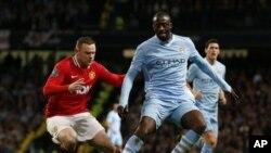 Yaya Toure na Manchester City (dama) yana kokawar kwallo da Wayne Rooney na Manchester United a karawar battar da suka yi litinin 30 Afrilu 2012, a filin wasa na Etihad dake birnin Manchester a Ingila, inda City ta doke United da ci 1-0.
