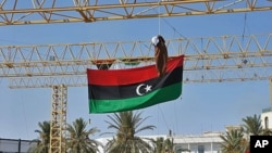 的黎波里街頭的國旗與懸吊的卡扎菲假人