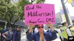 """Un manifestantes porta un cartel con el eslógan """"Fin del militarismo"""" en defensa de la paz en la península coreana cerca de la embajada de EE.UU. en Seúl, Corea del Sur."""