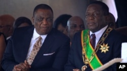 Zimbabwean President Emmerson Mnangagwa right, sits with his Deputy Constantino Chiwenga during a Heroes' Day event to commemorate the lives of those who died in the southern African country's 1970s war against white minority rule, in Harare, Aug. 13, 201