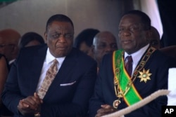 Zimbabwean President Emmerson Mnangagwa (R) sits with his Deputy Constantino Chiwenga during a Heroes' Day event to commemorate the lives of those who died in the southern African country's 1970s war against white minority rule, in Harare, Aug. 13, 2018.