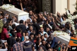 FILE - Relatives and friends carry the coffins of brothers Nadi Yousef Shehata, right, and Reda Yousef Shehata, two of the seven victims of an Islamic State ambush, in Minya, Egypt, Nov. 3, 2018.
