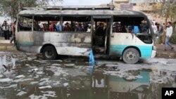 Warga memeriksa lokasi bom mobil bunuh diri di pasar di Sadr City, Baghdad, Irak (2/1). (AP/Karim Kadim)