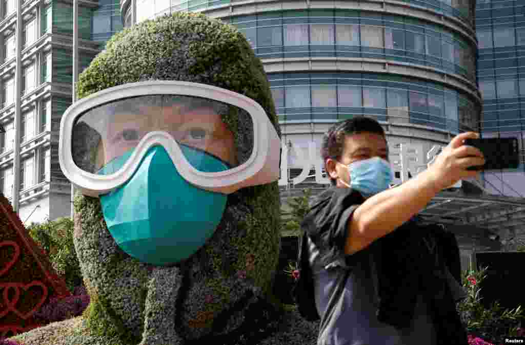 A man wearing a face mask takes selfies in front of a floral installation featuring a medical worker in the fight against the coronavirus disease, set up ahead of Chinese National Day on October 1, on Changan Avenue in Beijing, China.