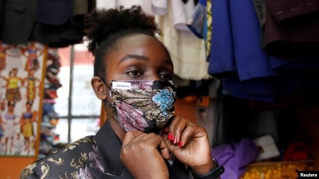 Kenyan fashion designer Ruth Martin fits a protective face mask as part of her latest creation inside her studio, as a measure to stem the growing spread of the coronavirus disease (COVID-19) outbreak, in downtown Nairobi, Kenya April 9, 2020. REUTERS/Nje