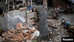一名婦人4月22日在地震災區蘆山縣推著自行車越過滿地的瓦礫。