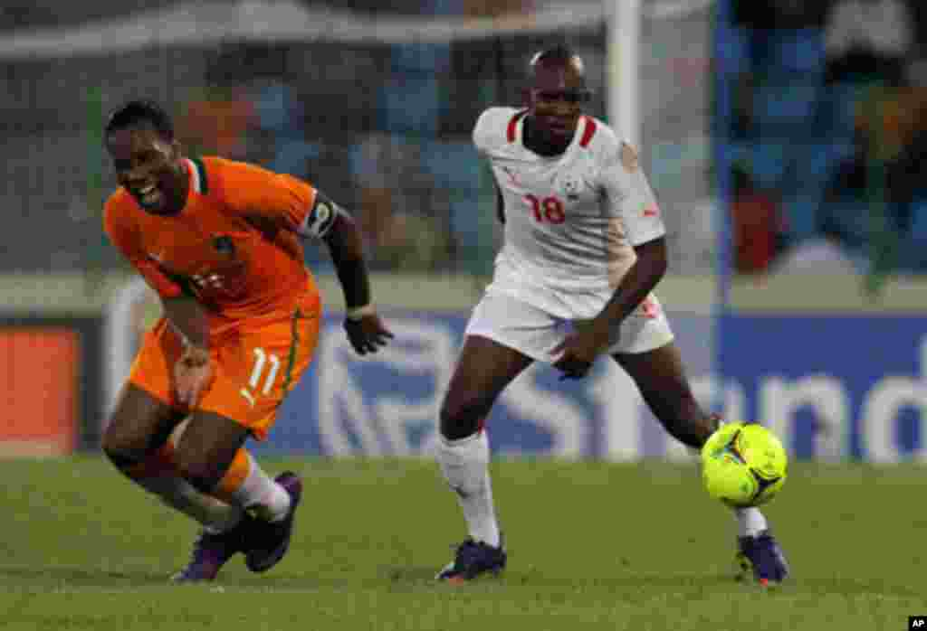 Drogba of Ivory Coast fights for the ball with Kabore of Burkina Faso during their African Nations Cup soccer match in Malabo