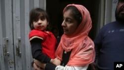 پولیس فائرنگ سے قتل ہونے والے خاندان کی بچی ہادیہ خلیل ایک رشتے دار خاتون کی گود میں (فائل فوٹو)