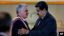 "Cuba's President Miguel DIaz-Canel, left, is embraced by his Venezuelan counterpart Nicolas Maduro after being awarded the ""Orden del Libertador Simon Bolivar,"" at Miraflores Presidential Palace in Caracas, Venezuela, May 30, 2018."