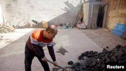 Un homme amasse du charbon qu'il utilise pour chauffer sa maison dans le village de Heqiaoxiang, province d'Hebei, Chine, le 5 décembre 2017.