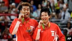 Pasangan ganda campuran Indonesia, Tontowi Ahmaddan Liliyana Natsir berpose dengan medali emas yang mereka raih di Olimpiade Rio, Rabu (17/8) bertepatan dengan HUT Kemerdekaan RI ke-71.