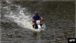 Một người đàn ông cưỡi xe gắn máy dọc theo 1 con đường bị ngập lụt ở Bangkok, 5/11/2011