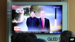 FILE - People watch a TV screen showing file footage of U.S. President Donald Trump, right, and North Korean leader Kim Jong Un.