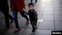 중국 상하이 중심가에서 한 남자 어린이가 부모와 함게 걷고 있다.
