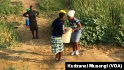 FILE: Bancedisana ukuthwala inkonxa zamanzi abawakhe emthonjeni koBulawayo. (Photo: VOA)