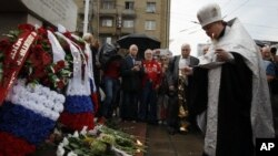 A Russian Orthodox priest prays as Moscovites light candles at a memorial to three men killed in the August 1991 hard line Communist coup attempt during a ceremony marking the 20th anniversary of the failure of the coup in downtown Moscow, Saturday, Aug.