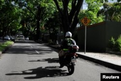 An employee of Pana, a mobile application which dispatches security crews to stranded drivers who request help, rides a motorbike on his way to assist a client in Caracas, Venezuela, June 15, 2018.