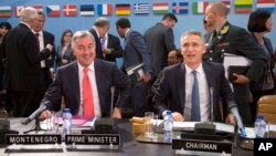 FILE - NATO Secretary General Jens Stoltenberg, right, and Montenegro's Prime Minister Milo Dukanovic, left, take their seats during a meeting of the North Atlantic Council and Montenegro at NATO headquarters in Brussels, May 19, 2016.