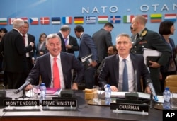 FILE - NATO Secretary-General Jens Stoltenberg, right, and Montenegro's Prime Minister Milo Dukanovic, left, take their seats during a meeting of the North Atlantic Council and Montenegro at NATO headquarters in Brussels, May 19, 2016.