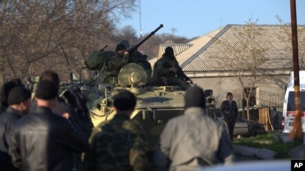 FILE - Soldiers in unmarked uniforms sit atop an APC at the gate of the Belbek base near the port city of Sevastopol, Crimea, March 22, 2014.