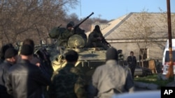 FILE - Soldiers in unmarked uniforms sit atop APC at the gate of the Belbek base near the port city of Sevastopol, Crimea, March 22, 2014.