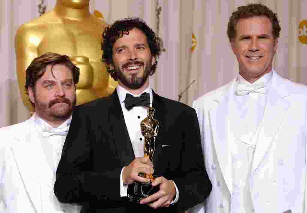 """Bret McKenzie, (al centro) recibe de Zach Galifianakis y Will Ferrell, el premio a mejor canción original, con el tema """"Man or Muppet""""."""