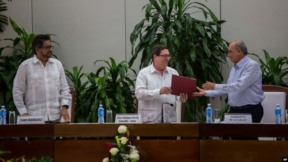 Cuba's Foreign Minister Bruno Rodriguez, center, gives a copy of the peace accord to Humberto de La Calle, right, head of Colombia's government peace negotiation team, as Ivan Marquez, left, chief negotiator of the Revolutionary Armed Forces of Colombia, or FARC, watches, after the signing of the latest text of the peace accord between the two sides in Havana, Cuba, Nov. 12, 2016.
