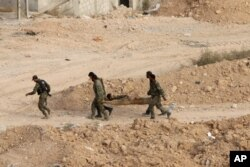 FILE - Syrian soldiers carry a wounded comrade on a stretcher in Harasta, northeast of Damascus, Syria, Oct. 22, 2015.