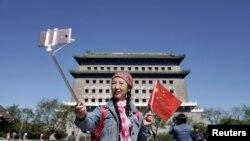 중국 베이징의 관광 명소인 정양문 앞에서 오성홍기를 든 여성이 사진을 찍고 있다. (자료사진)