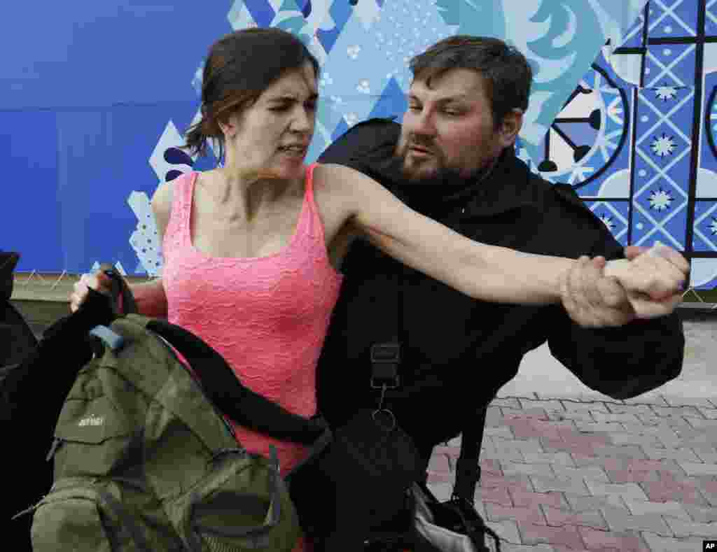 Nadezhda Tolokonnikova is pulled away by a Russian security officer after she and fellow members of the punk group Pussy Riot staged a protest performance, Sochi, Russia, Feb. 19, 2014.