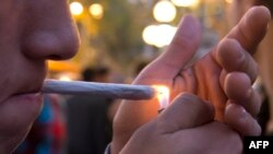 FILE - A young man lights a marijuana cigarette during a demonstration demanding a new law on cannabis in Montevideo, May 8, 2013.